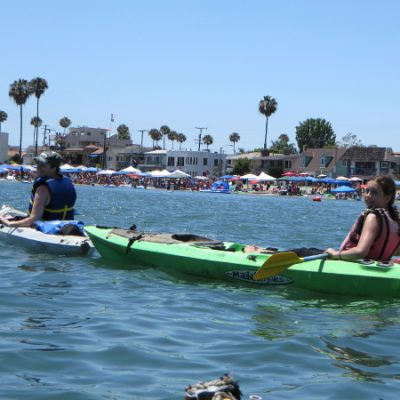 Two people in a kayak with people celebrating