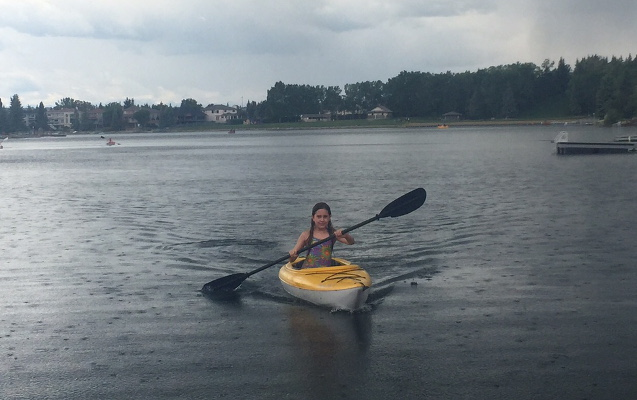 Girl kayaking in the rain